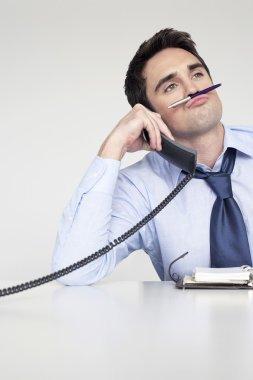 Businessman balancing pen on upper lip