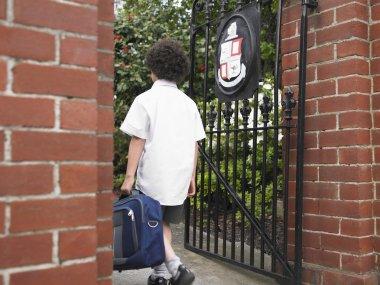 Elementary schoolboy walking through gate