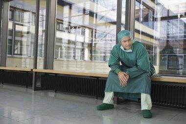 Pensive Physician sitting in hospital corridor stock vector