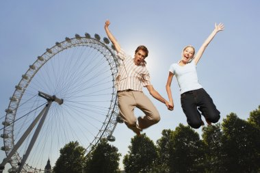 Couple jumping in front of London Eye