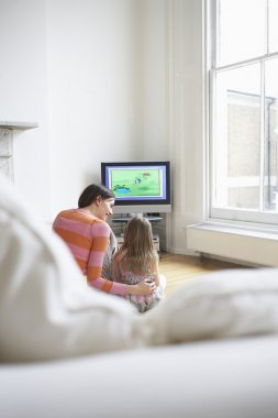 Mother and daughter watching cartoons in television