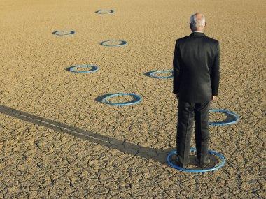 Businessman standing in hoops in desert