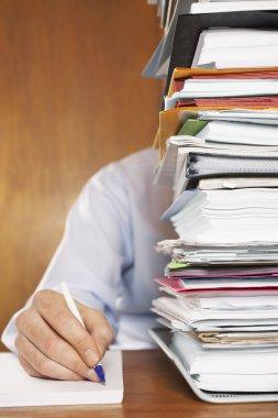 Man behind stack of paperwork