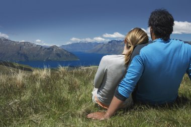Couple cuddling looking over lake and hills