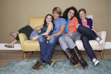 Friends sitting arms around one another on sofa