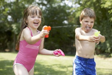 Girl and boy with water pistols