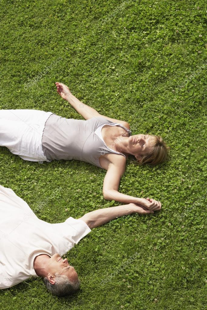 Couple sleeping on grass