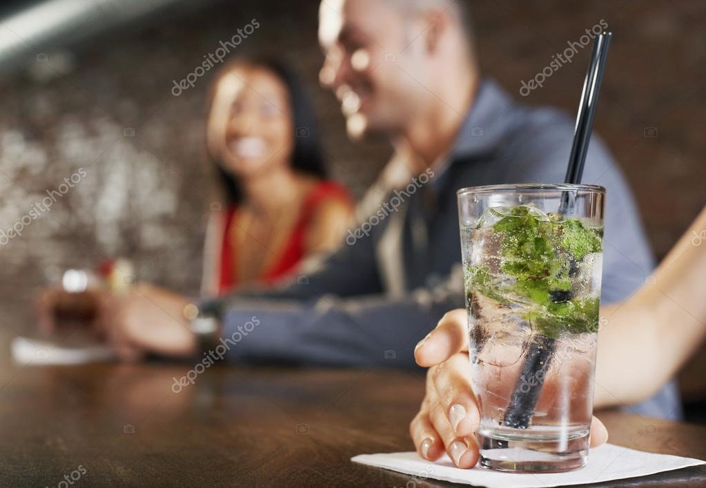 Couple sitting at bar cocktail glass