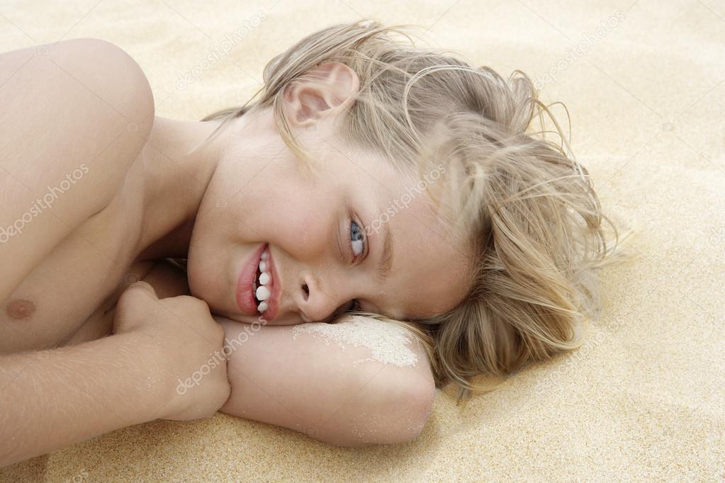 Preteen blond boy on sand