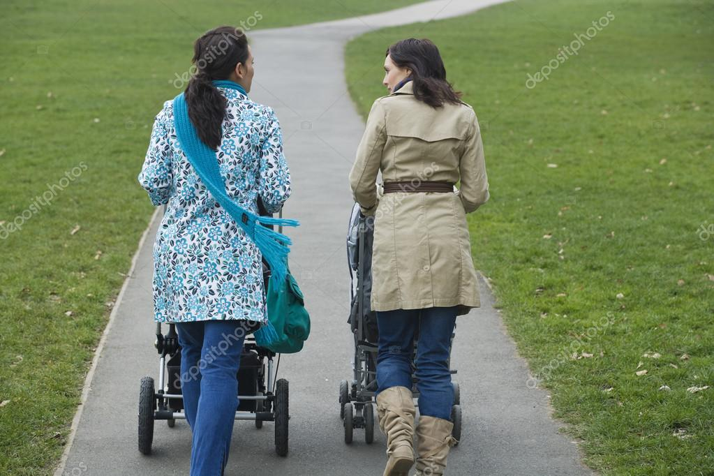 Mothers pushing strollers in park
