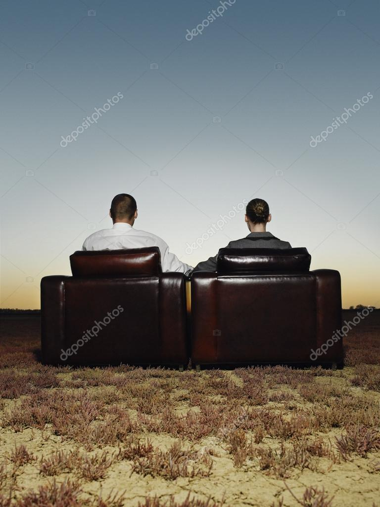 Business people in armchairs in open plain