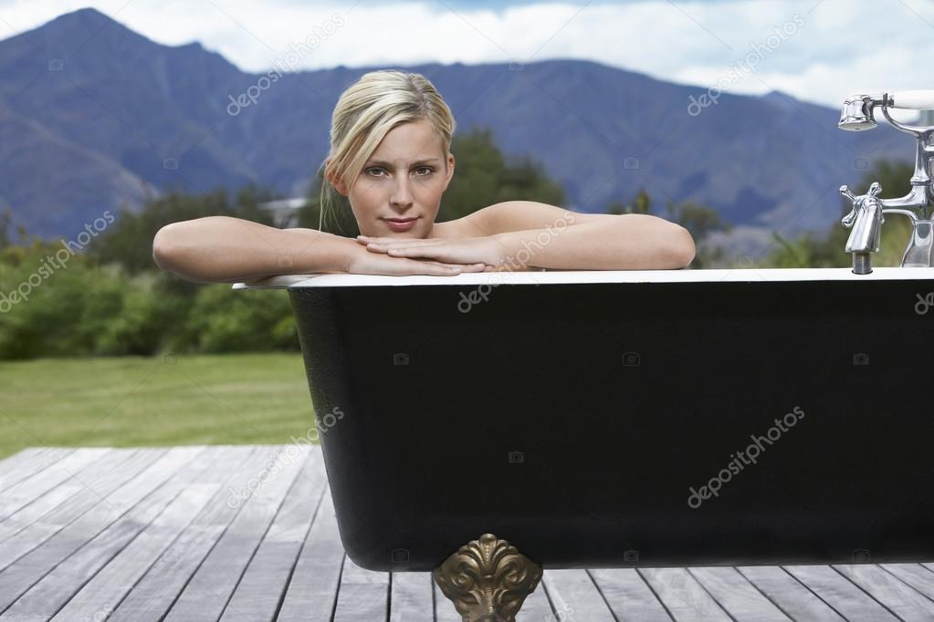 Woman in bathtub on porch