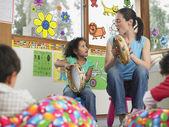 Učitel hraje tamburíny s dítětem