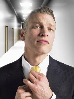 Man adjusting tie in corridor