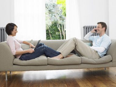 Couple reclining on couch
