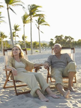 Senior couple relaxing on deckchairs