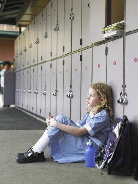 Elementary schoolgirl sitting on floor