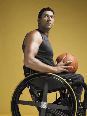 Paraplegic athlete holding basketball