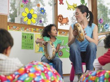 Teacher playing Tambourines with child