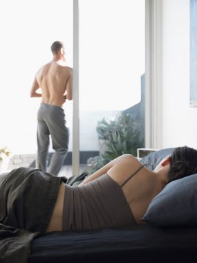 Man standing and Woman lying on bed