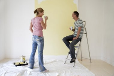 Couple drinking coffee and admiring painted wall