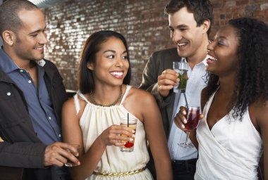 Two couples holding drinks standing in bar