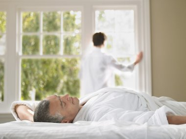 Man in bed wife looking through window
