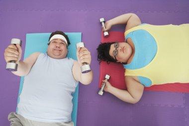 Man and woman lifting dumbbells