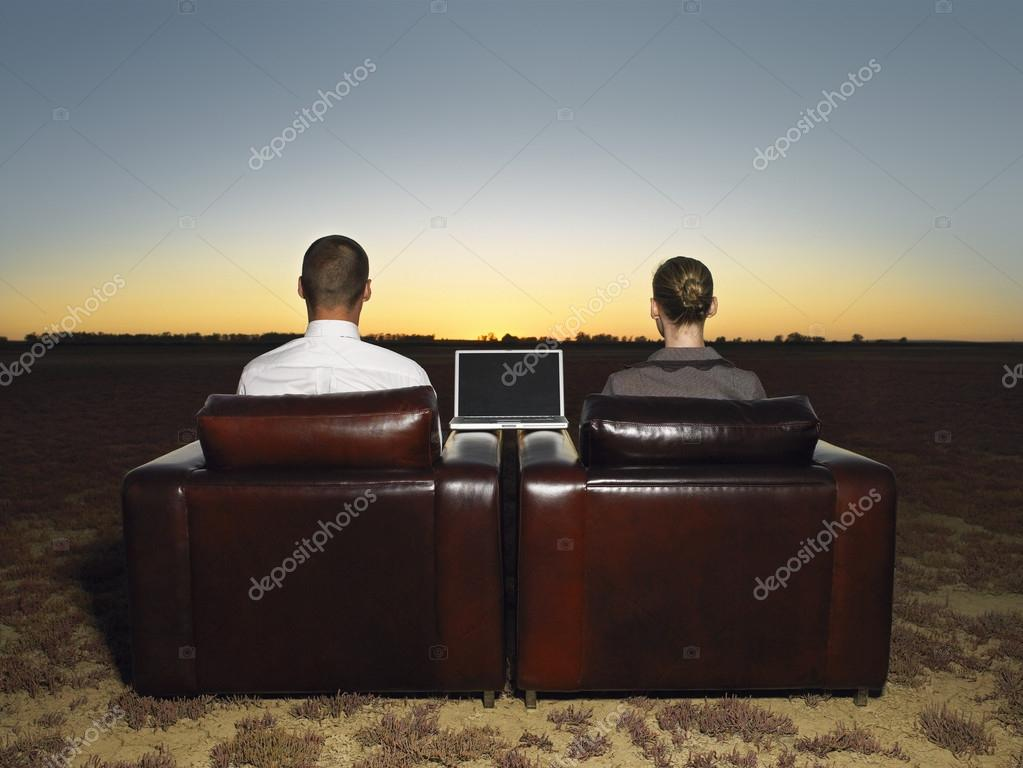Business people sitting in armchairs in open plain