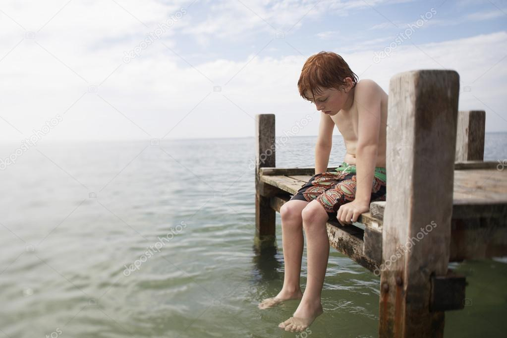 Pre-teen boy sitting on pier