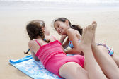 Pre-teen girls lying on beach