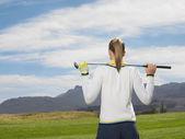 Žena stojící na golfovém hřišti
