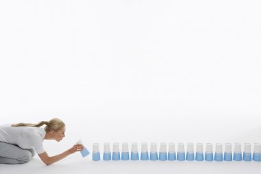 Woman lining up plastic cups on ground against white background stock vector