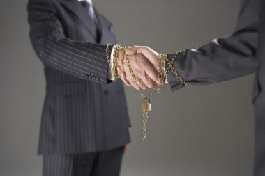 Businessmen shaking hands wrapped in gold chain