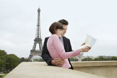 Couple reading map in front of Eiffel Tower