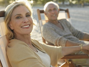 Woman with man relaxing on deckchairs