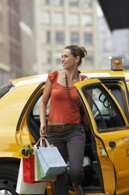 Woman with shopping bags exiting taxi