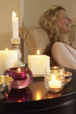 Woman on sofa beside table with Candles