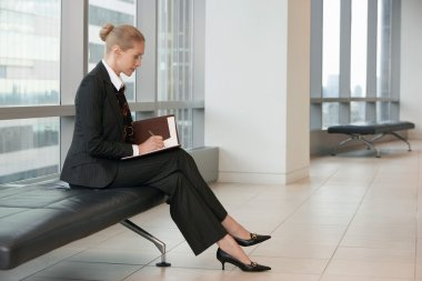 Businesswoman writing in planner