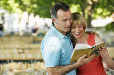 Couple in park looking at book