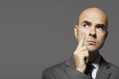 Bald businessman with hand on chin thinking