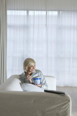 Woman watching television and eating ice cream