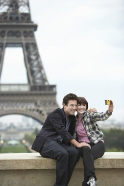 Couple taking self portrait  in front of Eiffel Tower