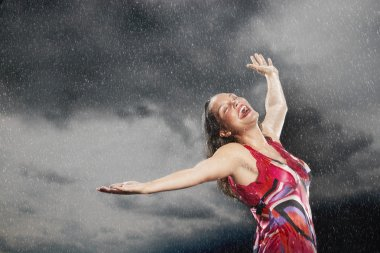 Woman arms outstretched  in rain