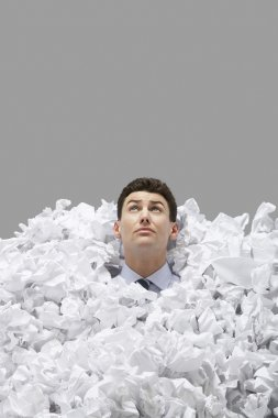 man covered in crumpled paper
