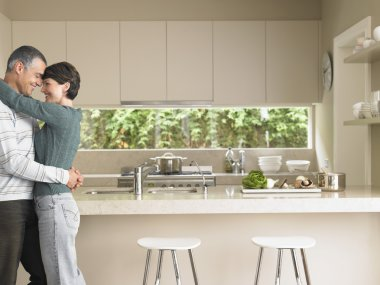 Man and woman embracing in kitchen
