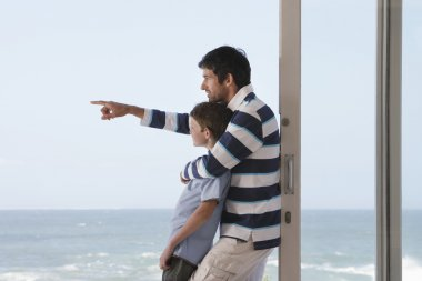 Father pointing  out to sea