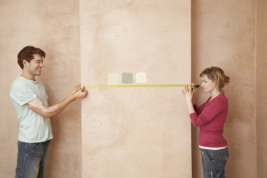 Couple Measuring Wall Before Painting