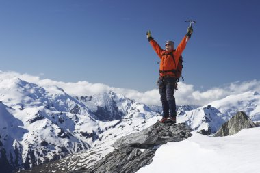 Mountain climber with arms raised