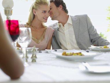 Couple Whispering at Dinner